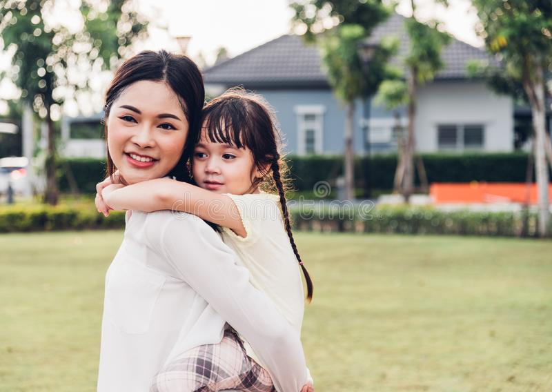Family happy children kid son girl kindergarten playing ride back piggyback mother mom. On outdoors park stock photo