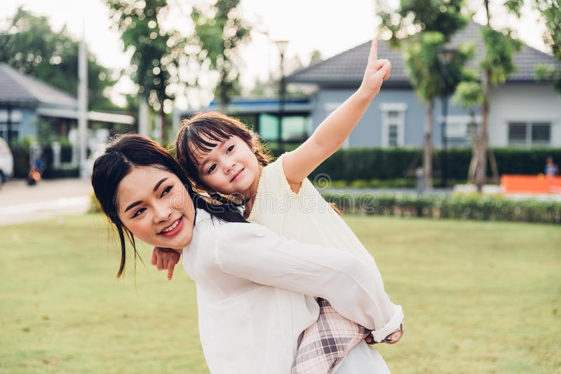 Family happy children kid son girl kindergarten playing ride back piggyback mother mom. On outdoors park royalty free stock photos