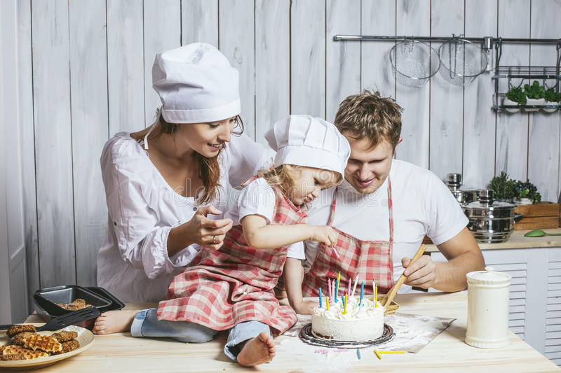 Family, happy daughter with mom and dad at home in the kitchen l. Aughing and baking a birthday cake together, with love royalty free stock image