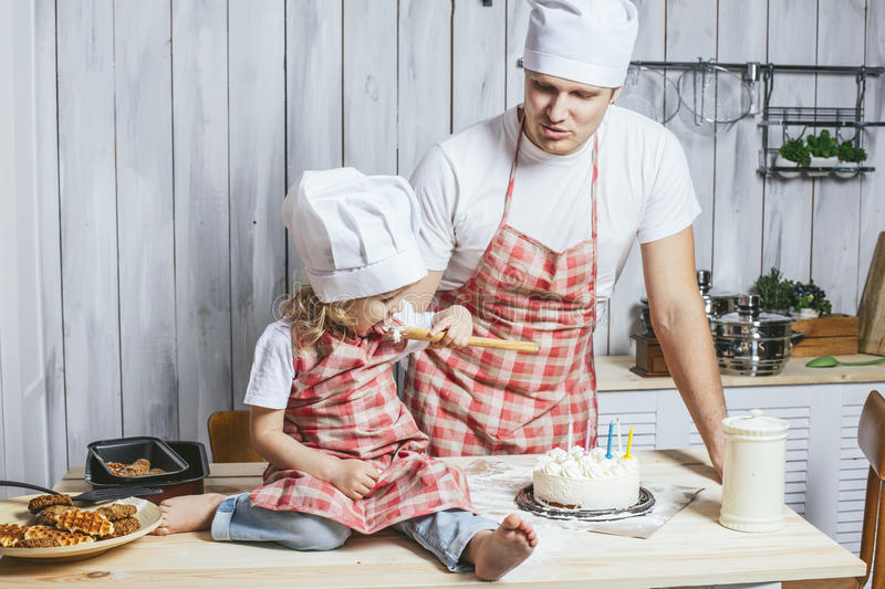 Family, happy daughter with my dad at home in the kitchen laughing and baking a birthday cake together stock image