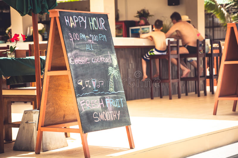 Family during happy hours at tropical beach cafe with signboard during summer beach holidays stock photography
