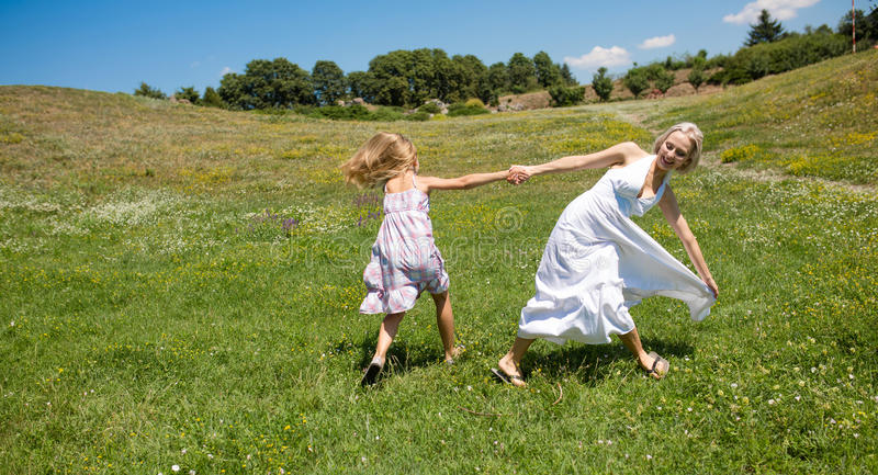 Family harmony, mom and daughter rejoicing outdoors. stock images