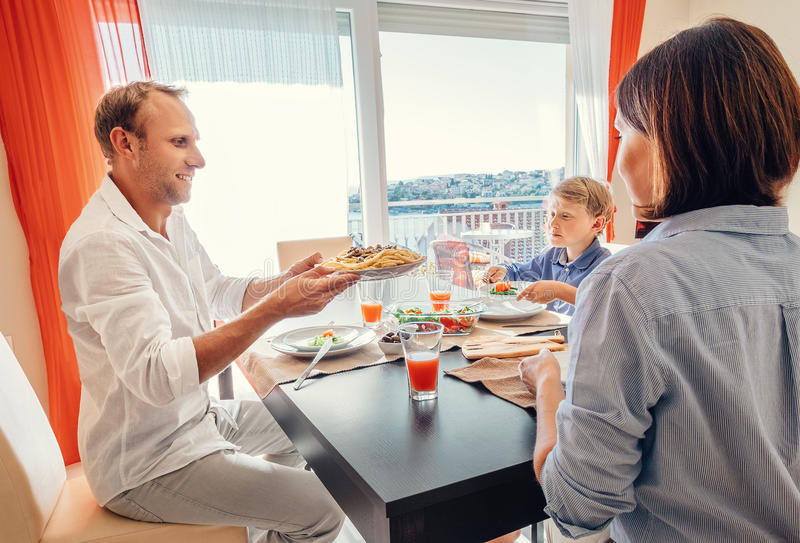 Family has a fresh cooking meal at dinner time royalty free stock photo