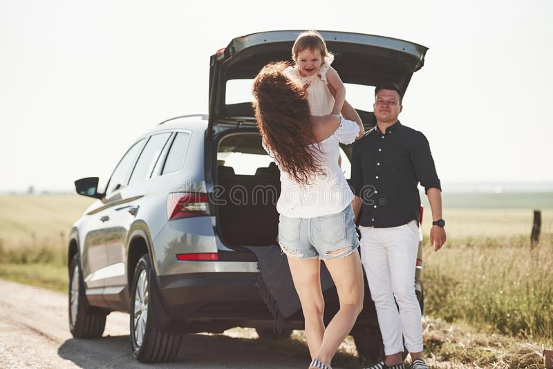 Family have some good time at countryside near silver automobile at sunset stock image