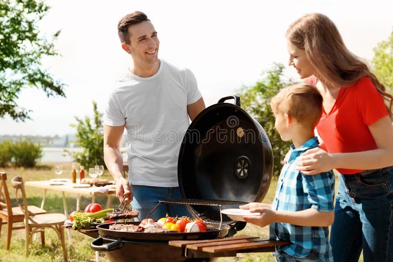 Family having barbecue with modern grill outdoors. Happy family having barbecue with modern grill outdoors royalty free stock image