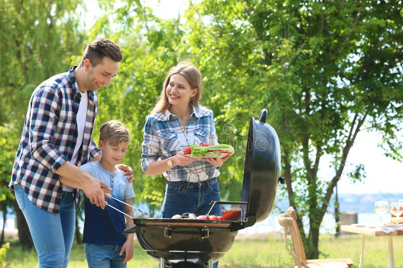 Family having barbecue with modern grill outdoors. Happy family having barbecue with modern grill outdoors royalty free stock photography