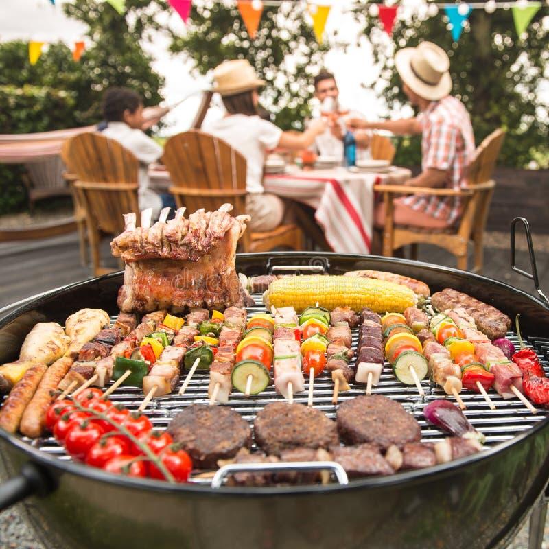 Family Having A Barbecue Party In Their Garden Stock Photo