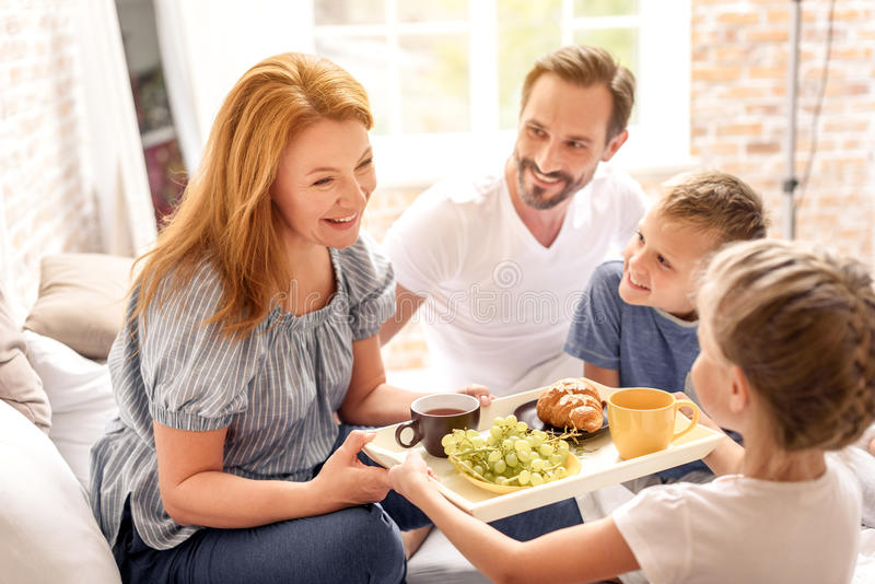 Family having breakfast at home. Sweet moments. mother holding in hands tray with breakfast and looking at her daughter with smile royalty free stock photo