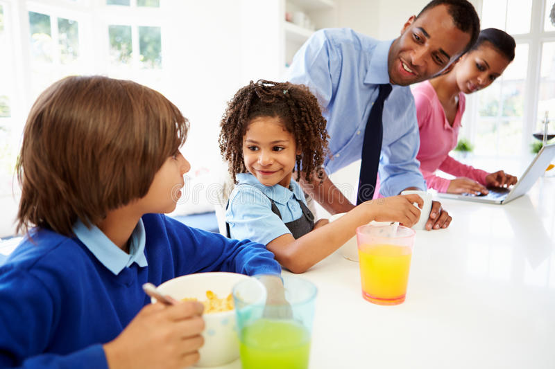 Family Having Breakfast In Kitchen Before School And Work. Eating Cereal Whilst Looking At Each Other royalty free stock photography