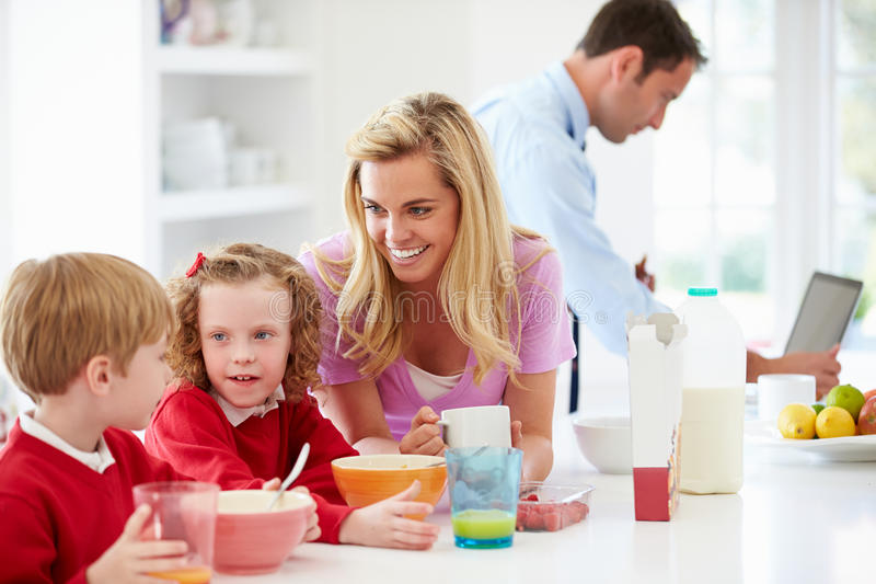 Family Having Breakfast In Kitchen Before School And Work. Sitting At Table Talking stock photos