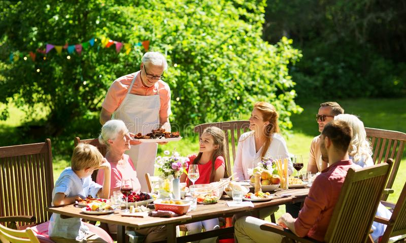 Family having dinner or barbecue at summer garden royalty free stock photo