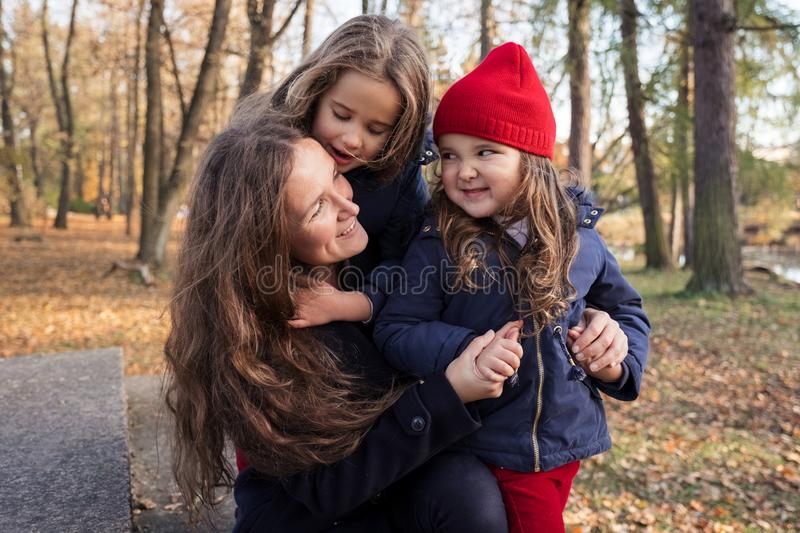 Family having fun in autumn park outdoors, hugging, laughing, relaxing, enjoy life. Adult mother embracing little daughters. Close royalty free stock photography