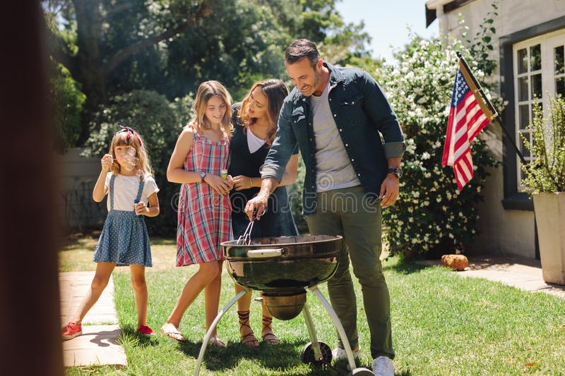 Family having fun cooking food together in the backyard stock images