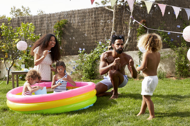 Family Having Fun In Garden Paddling Pool royalty free stock photography