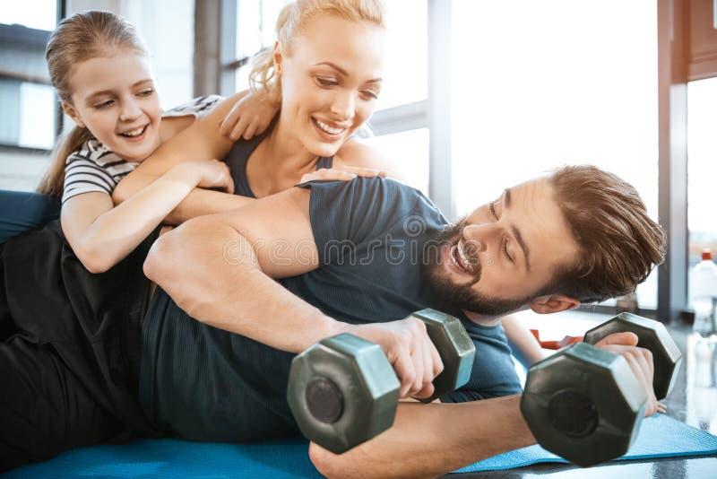 Family having fun at gym, man holding dumbbells. Happy family having fun at gym, men holding dumbbells royalty free stock photo