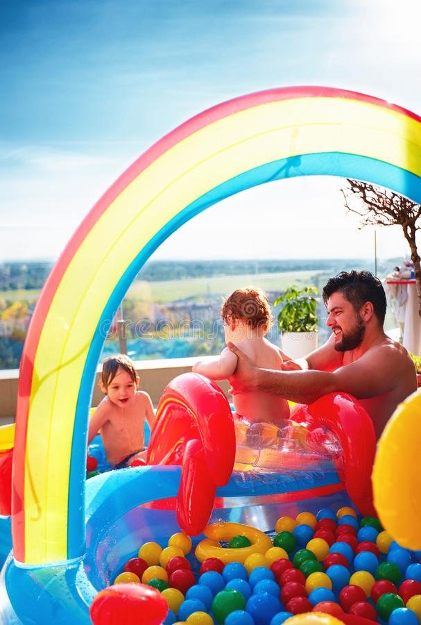 Family having fun in inlatable pool with slide and lots of colorful balls royalty free stock image