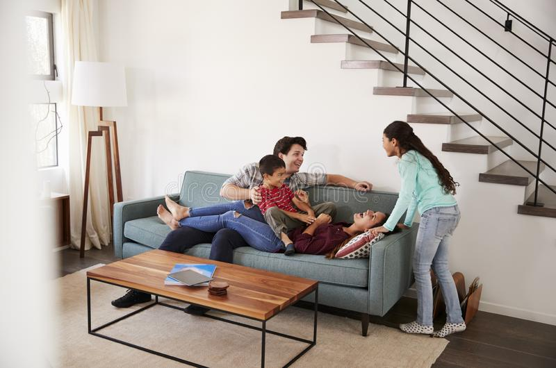 Family Having Fun Lying On Sofa At Home Together stock photo