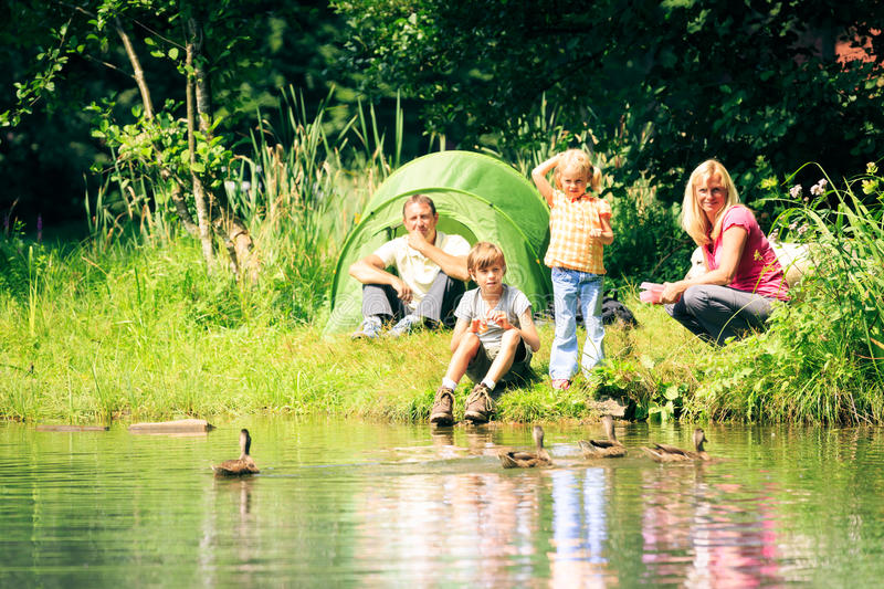 Family Having Fun Outdoors. A family is camping by the lakeside royalty free stock images