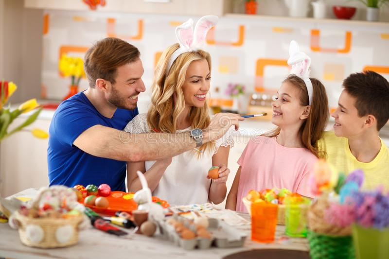 Family having fun while painting Easter eggs stock images
