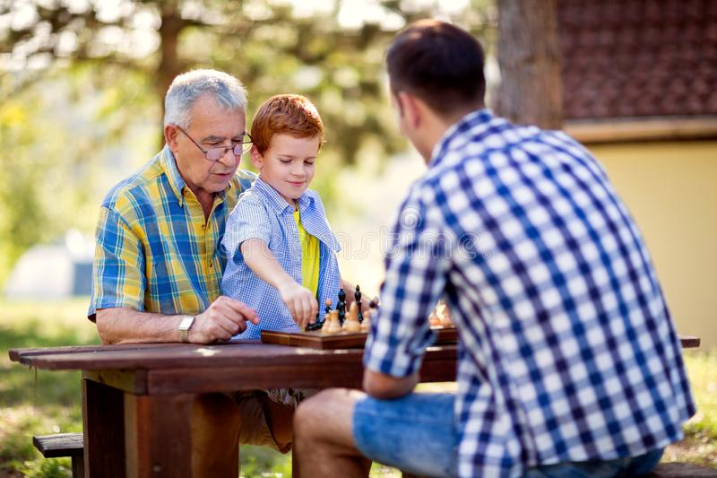 Family having fun and playing chess. At park stock photo