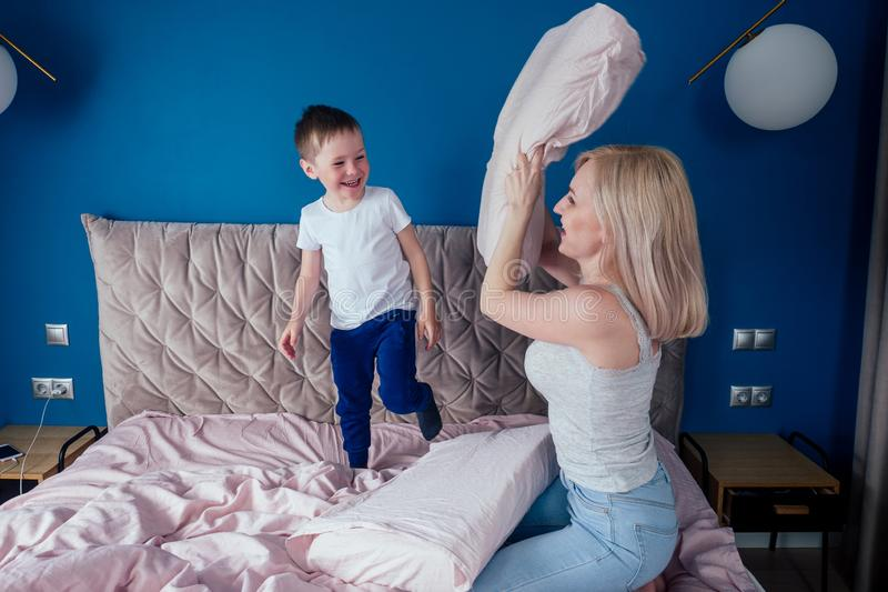 Family having fun together at the weekend together.Mother and child on bed. blonde mom and baby boy playing pillow fight royalty free stock photography