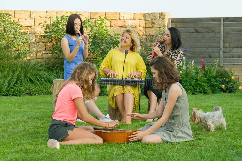 The family is having fun, two mothers with teenage daughters are singing and using musical instruments, family music. Band, sitting on the lawn near the house stock image
