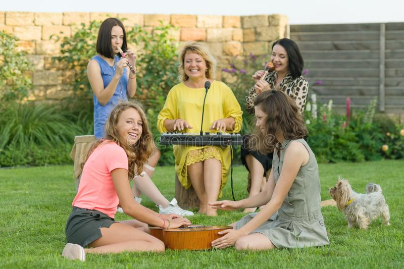 The family is having fun, two mothers with teenage daughters are singing and using musical instruments, family music band, sitting. On the lawn near the house royalty free stock image