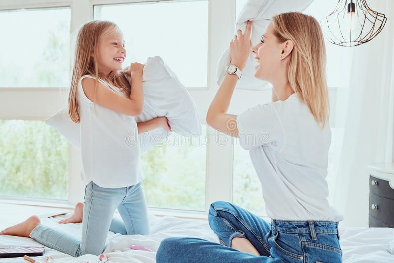 Family having funny pillow fight on bed. Beautiful mom with her little cute daughter spending free time together stock image