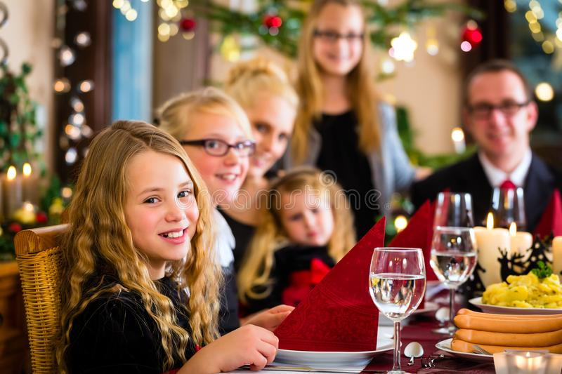 Family having German Christmas dinner. German Mother, father, children celebrating Christmas eve with traditional dinner Wiener sausages and potato salad royalty free stock images