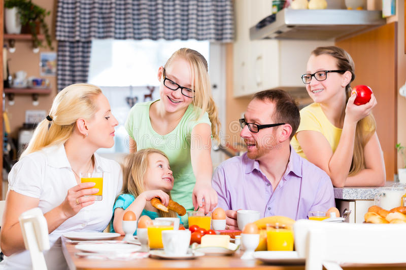 Family having joint breakfast in kitchen. Eating and drinking stock photography