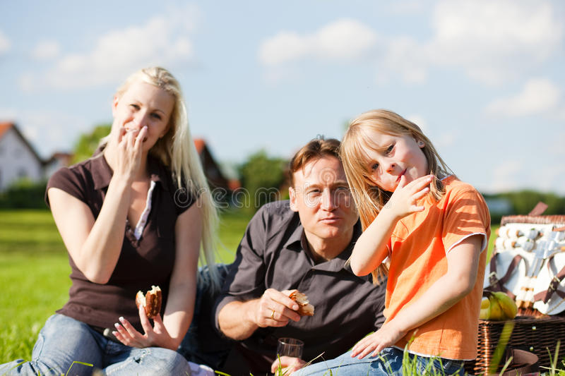 Family having picnic. Family - father, mother and daughter child - having a picnic on a green meadow on a beautiful and bright summer day royalty free stock photos