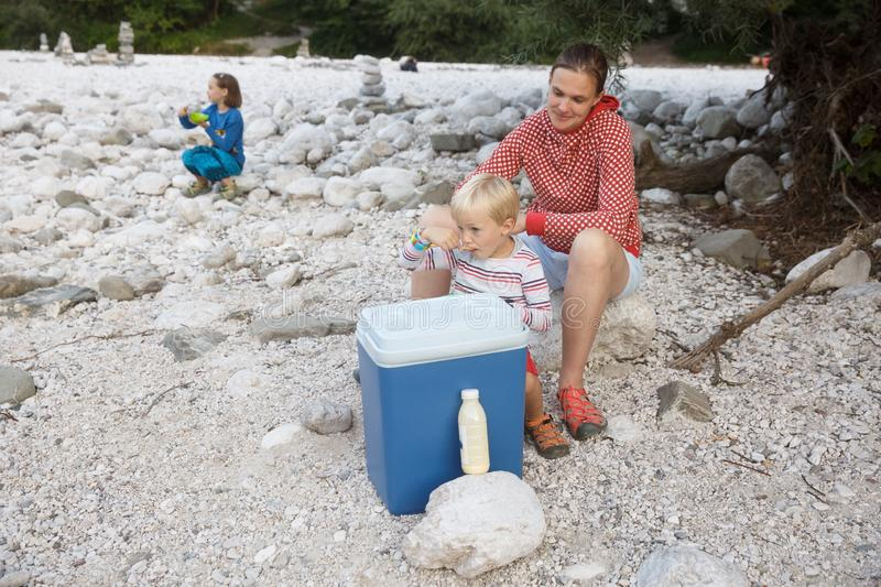Family having a picnic in nature out of a cool box, sitting on the river bank royalty free stock image