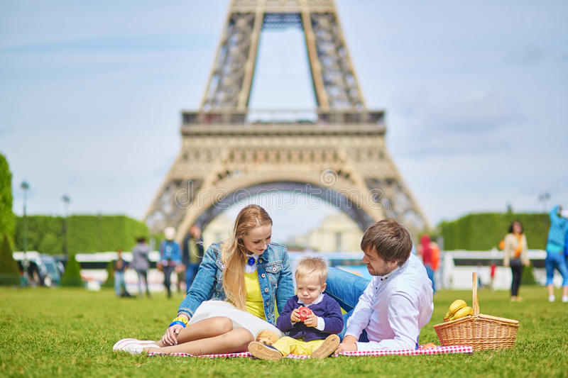 Family having picnic in Paris. Happy family of three, mother, father and little toddler boy, having picnic in Paris near the Eiffel tower royalty free stock images
