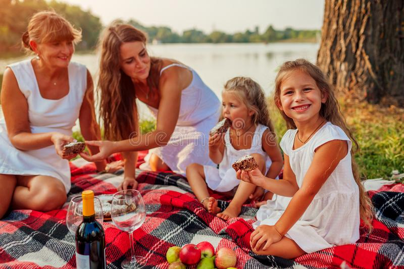 Family having picnic by summer river at sunset. Mother, grandmother and kids eating cake. Three denerations stock photos