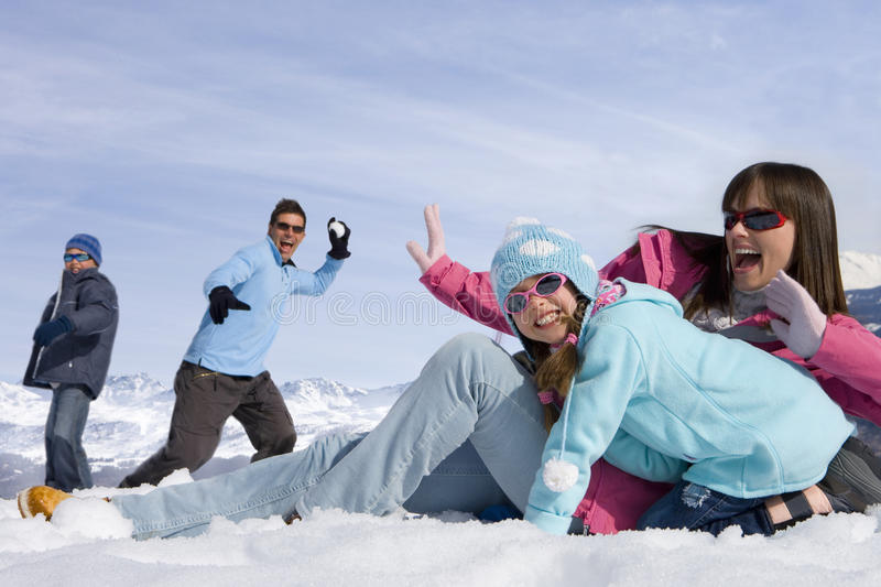 Family having snowball fight in the snow royalty free stock image