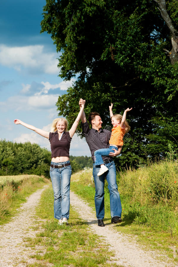 Family Having A Walk Carrying Child Royalty Free Stock Photo