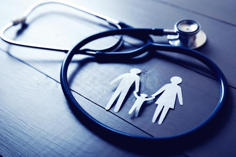 Family health care and insurance concept. Stethoscope and paper cut family stock photo