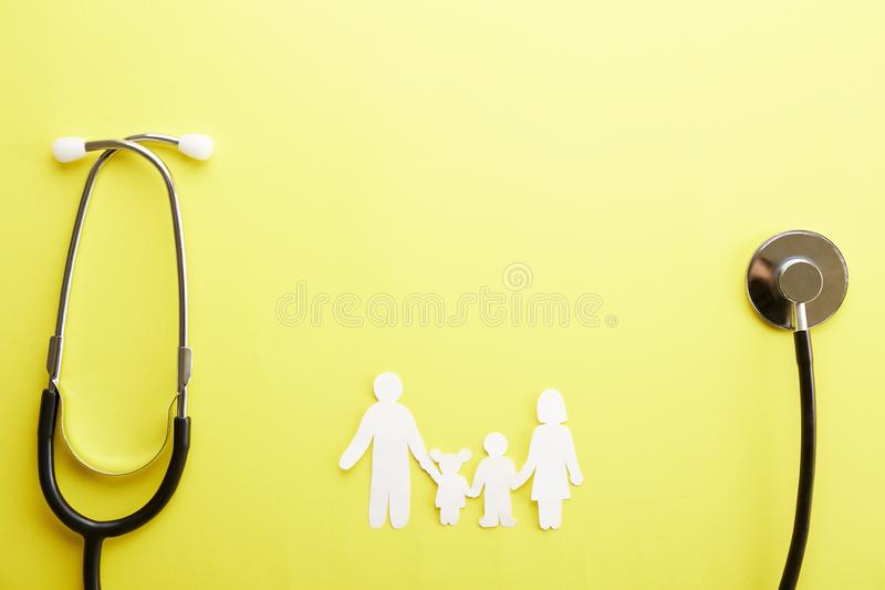 Conceptual image of paper chain in form of family. health insuarance accessories. Family health / life insurance concept. Paper chain in form of family, mother stock photo