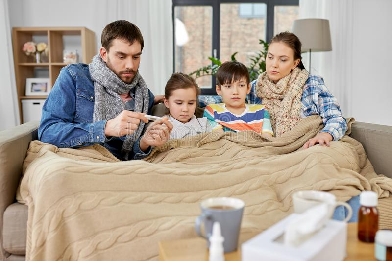Family with ill children having fever at home stock image