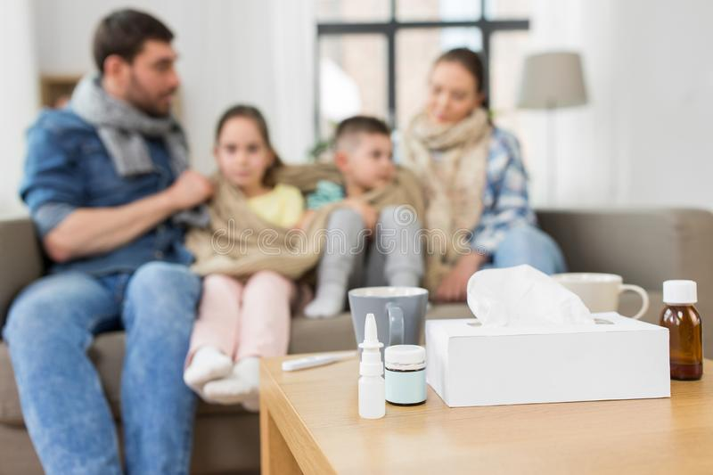 Medicines on table and ill family at home stock photos