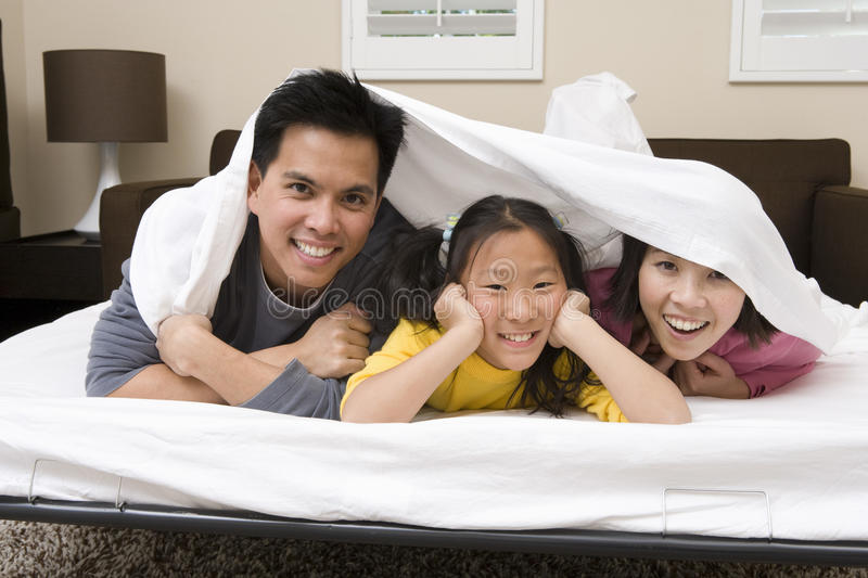 Family Hiding Under The Blanket. Portrait of a happy family hiding under the blanket in bedroom royalty free stock photos