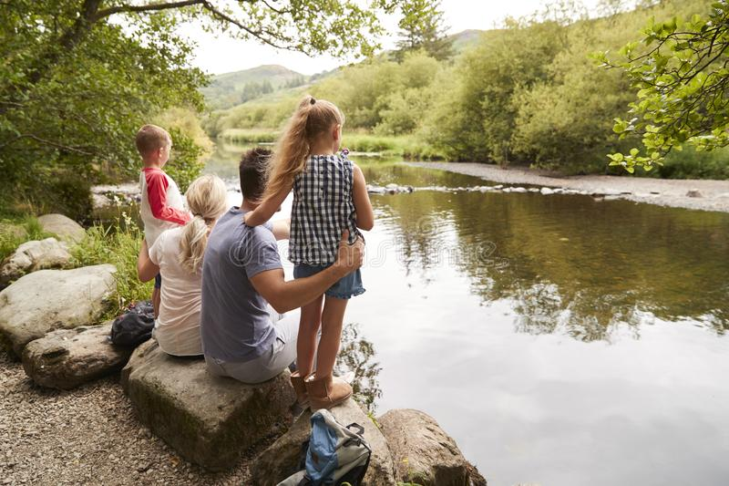 Family On Hike Looking Out Over River In UK Lake District stock images
