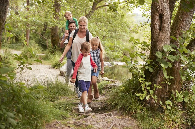 Family Hiking Along Path By River In UK Lake District stock photos