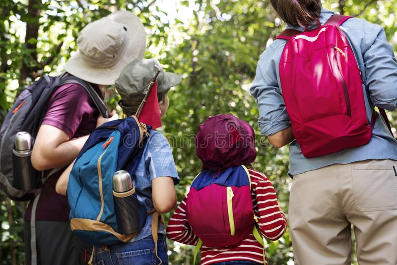 Family hiking with backpacks in forest royalty free stock image