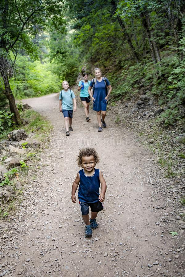 Family hiking on a scenic mountain trail talking to each other. Family hiking together along a scenic mountain trail on a summer day. Selective focus Lifestyle royalty free stock photo