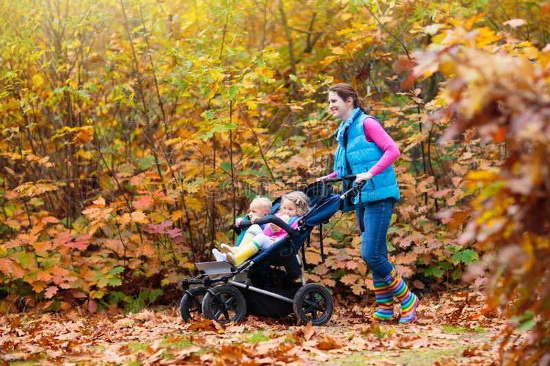 Family hiking with stroller in autumn park. Active mother, baby and toddler in twin double pushchair. Fit healthy mom walking with jogger pram and kids stock photo
