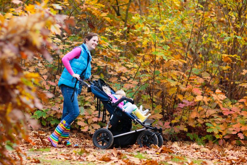 Family hiking with stroller in autumn park. Active mother, baby and toddler in twin double pushchair. Fit healthy mom walking with jogger pram and kids royalty free stock images