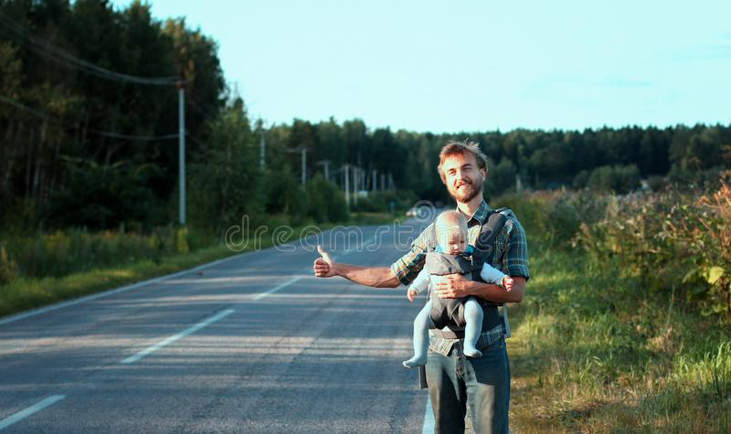 Family hitchhiking. Father with his little son wait for car. Family hitchhiking. Bearded father with his little son in baby carrier wait for car on the road royalty free stock image