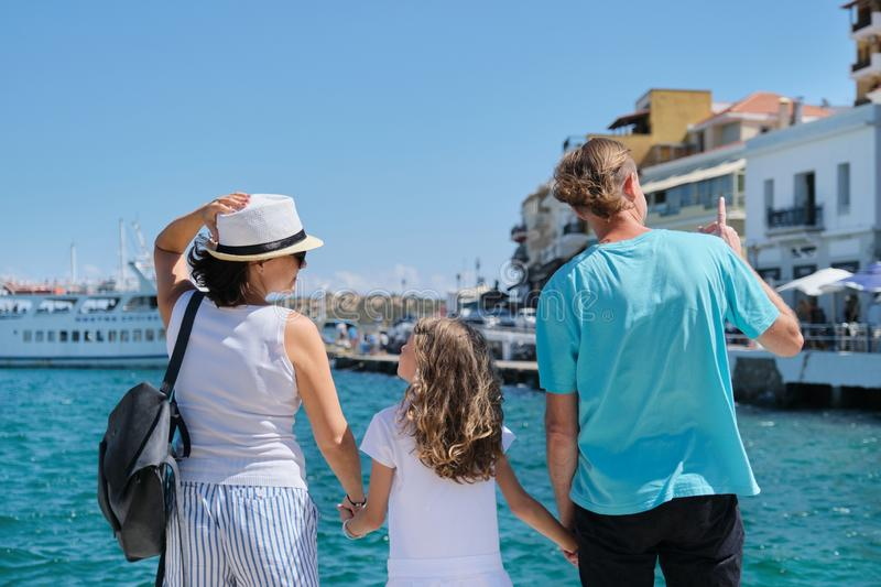 Family holding hands, back view, sea mediterranean vacation stock photos