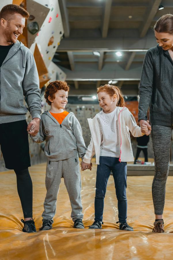 Full-length shot of happy family with kids holding hands and standing in a row. At gym stock photography